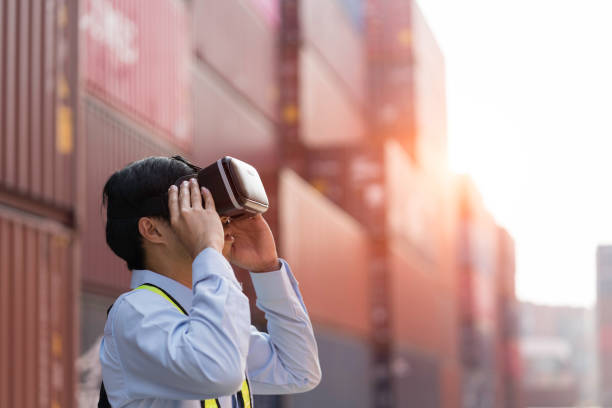 Businessman in virtual reality glasses and truck with cargo container on road in shipping yard stock photo