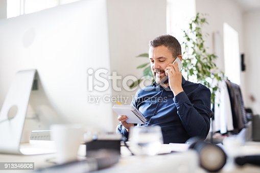 913346608 istock photo Businessman in wheelchair at the desk in his office. 913346608