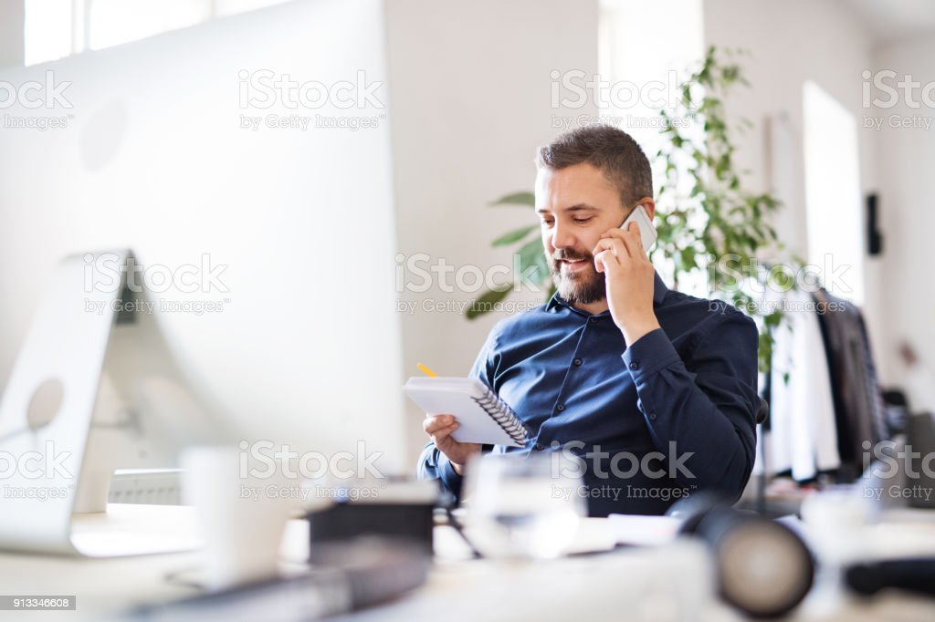 Kaufmann im Rollstuhl am Schreibtisch in seinem Büro. – Foto
