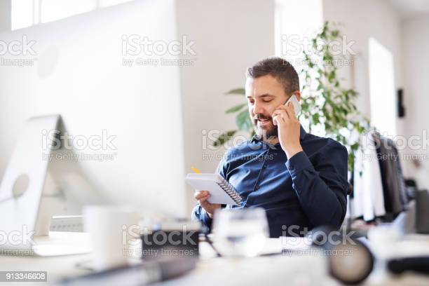 Businessman in wheelchair with smartphone at the desk in the office, making a phone call.