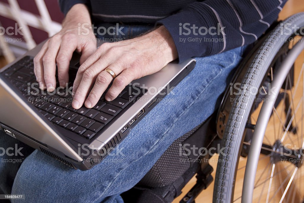 Businessman in wheelchair with computer (series) royalty-free stock photo