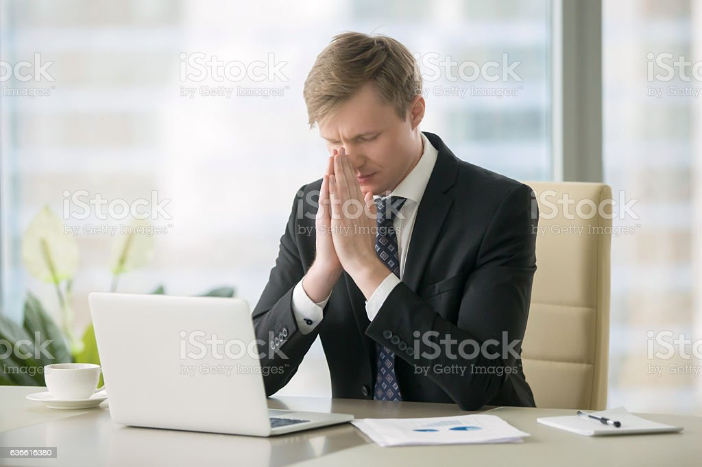 Businessman in yoga pose at the desk stock photo