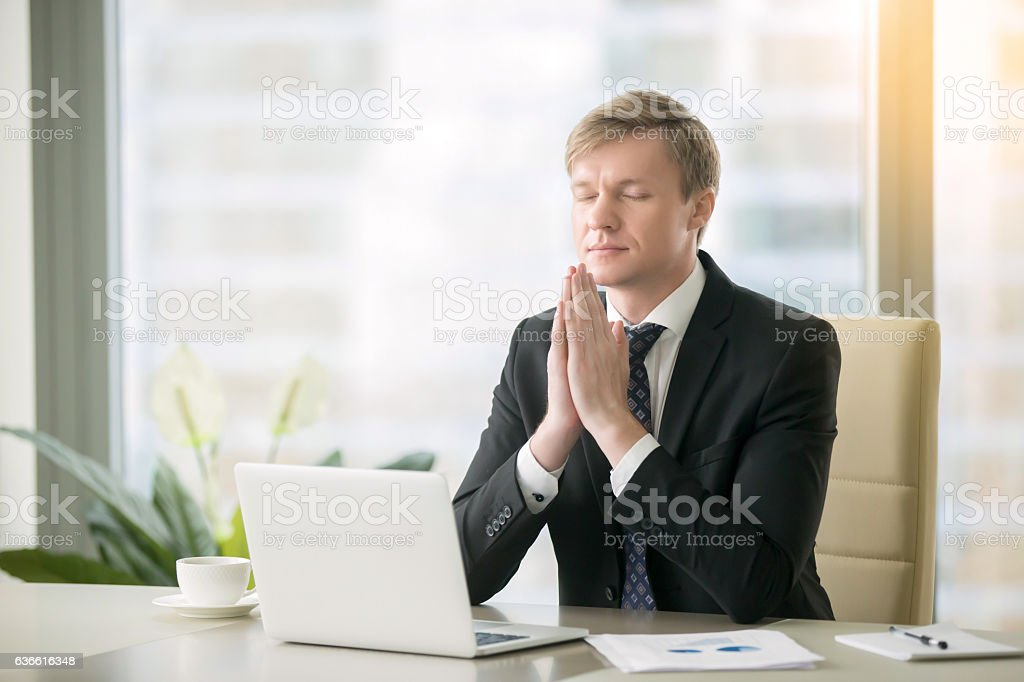 Businessman in yoga pose at the office desk stock photo