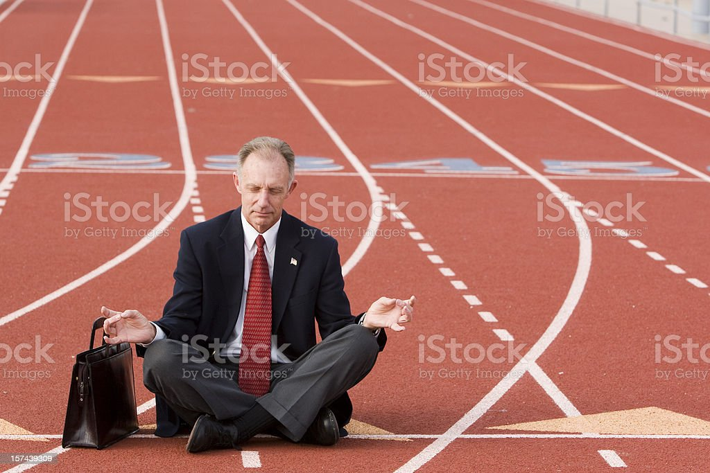 Businessman in yoga pose on sports track royalty-free stock photo