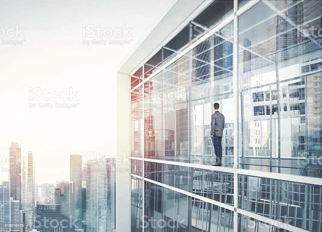 Businessman inside the house looking at city stock photo