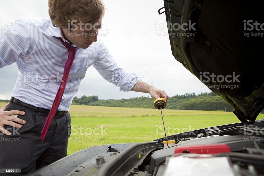 Businessman inspecting car oil royalty-free stock photo