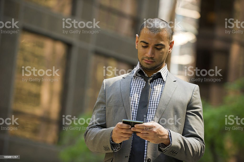 Businessman instant messaging on a smart phone stock photo