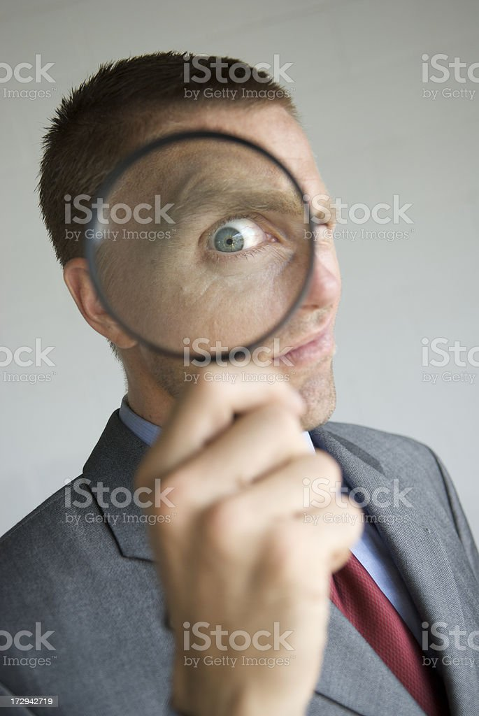 Businessman Investigates with Magnifying Glass royalty-free stock photo