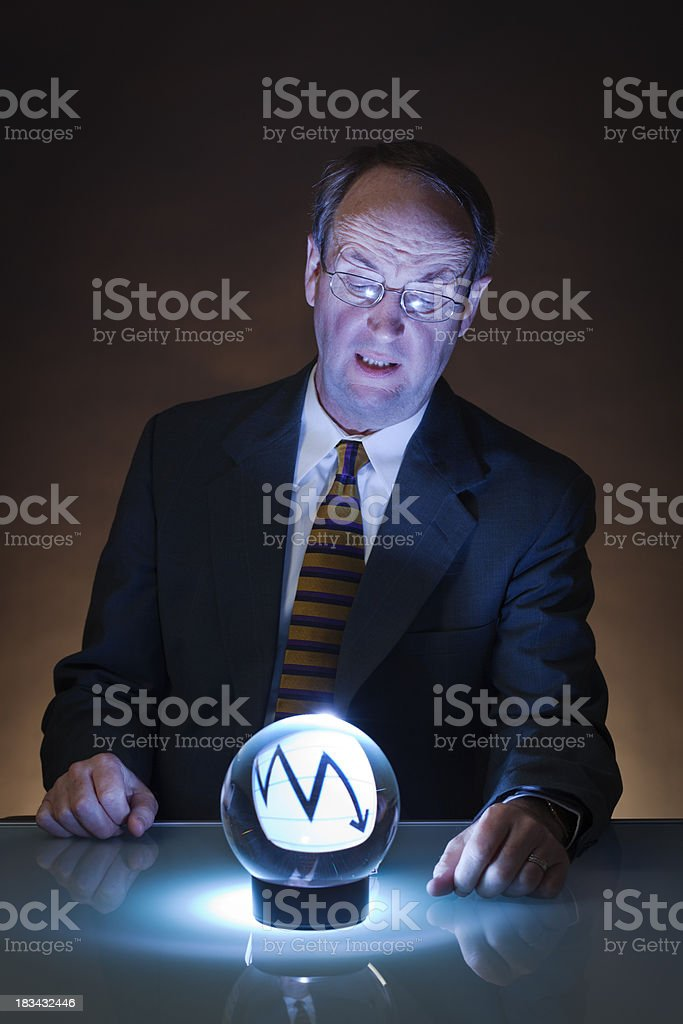Businessman Investor Predicting Downward Future of Economy in Crystal Ball royalty-free stock photo