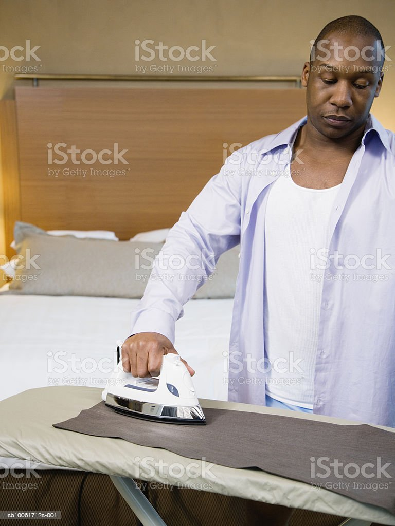 Businessman ironing trousers in hotel room 免版稅 stock photo