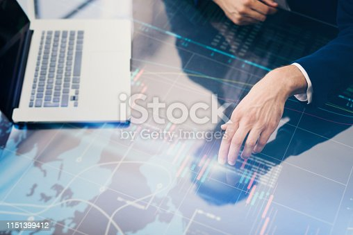 960164282 istock photo Businessman is analysing financial statistics on a screen of modern hi tech digital tablet. Male hands with futuristic gadget 1151399412