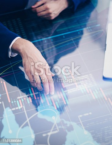 960164282 istock photo Businessman is analysing financial strategy on a screen of modern hi tech digital tablet. Male hands with futuristic gadget 1151399384