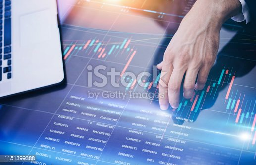 960164282 istock photo Businessman is analysing financial strategy on a screen of modern hi tech digital tablet. Male hands with futuristic gadget 1151399388