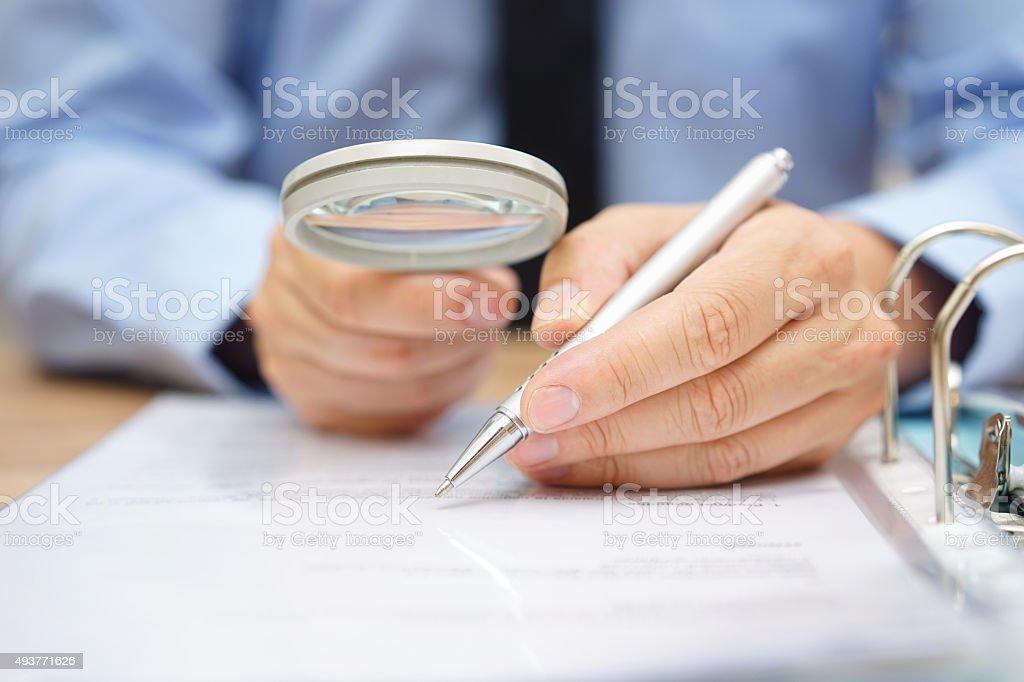 Geschäftsmann ist analysieren durch Lupe Vertrag und Preise – Foto