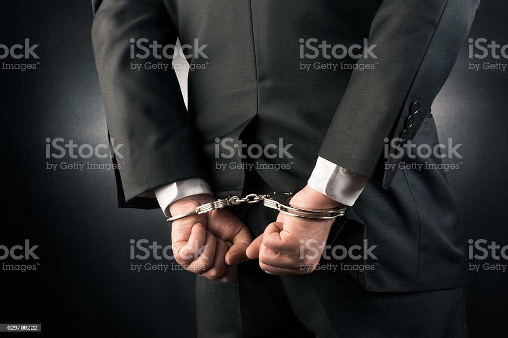 Businessman is arrested and handcuffed stock photo