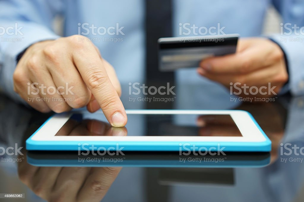 Empresario es comprar mercancías en tableta con tarjeta de crédito - foto de stock
