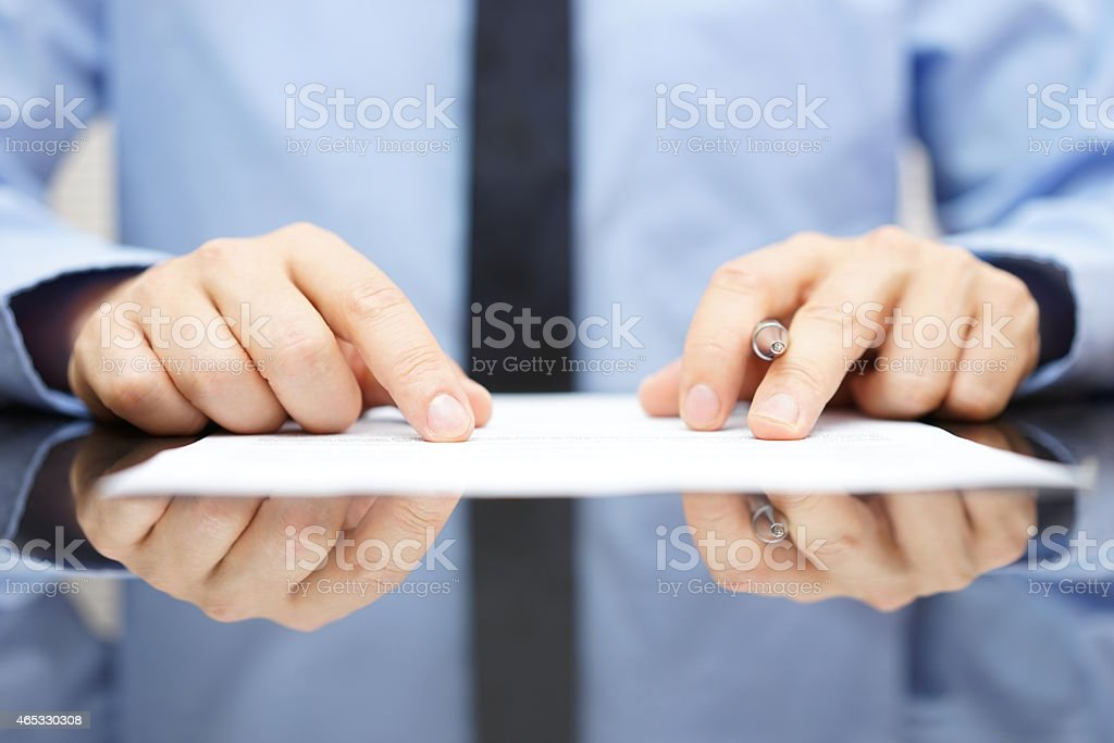 businessman is carefully reading contract stock photo