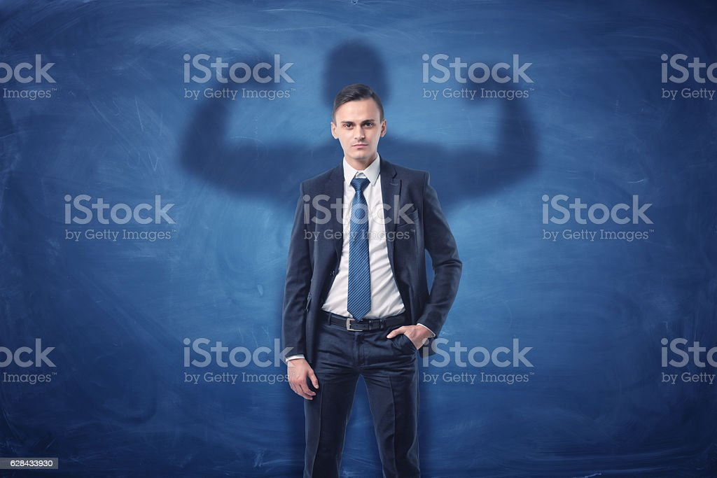 Businessman is casting shadow of big strong muscular man showing stock photo