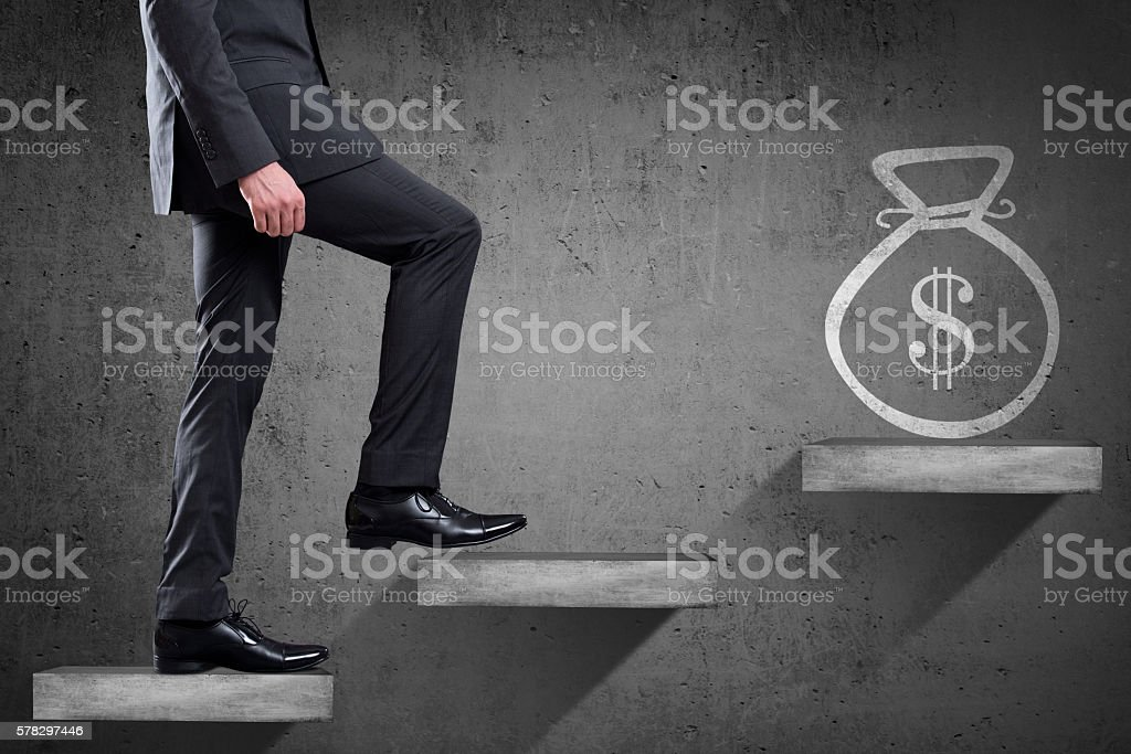 Businessman is climbing up to get dollar bag stock photo