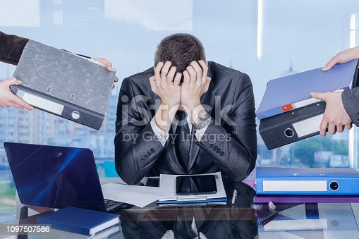 istock A businessman is closing his face with his hands in working stress assault. 1097507586