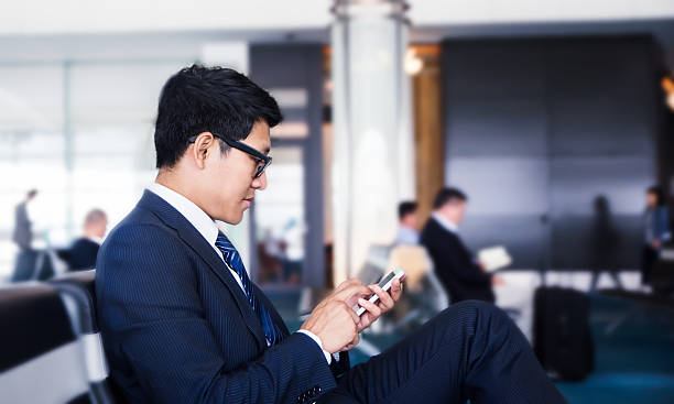businessman is Doing Business on mobile phone, while business man is Doing Business on mobile phone, while is sitting in Airport near window with sun rays during his business trip. air transport building stock pictures, royalty-free photos & images