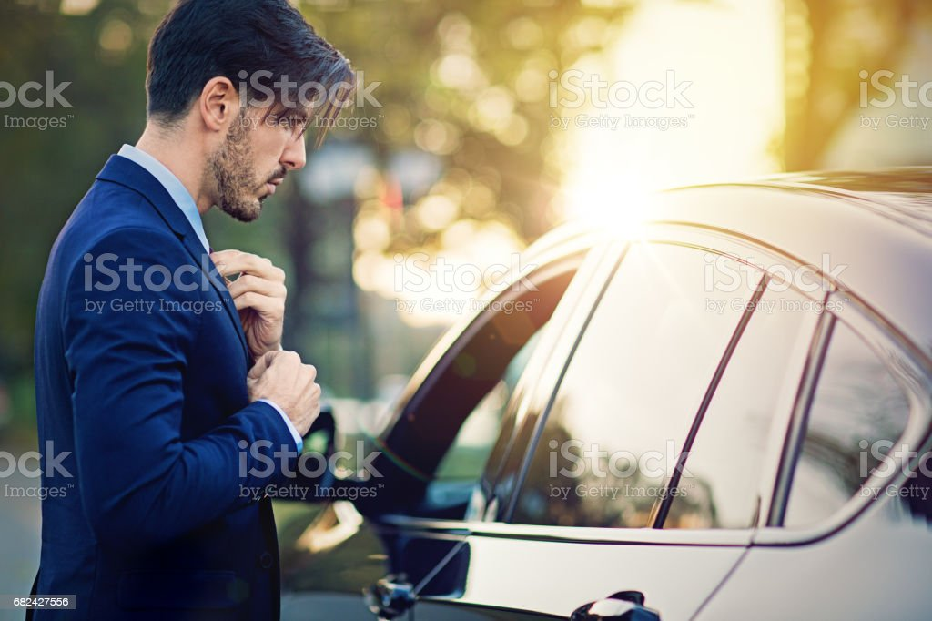 Businessman is fixing his necktie before a meeting royalty-free stock photo