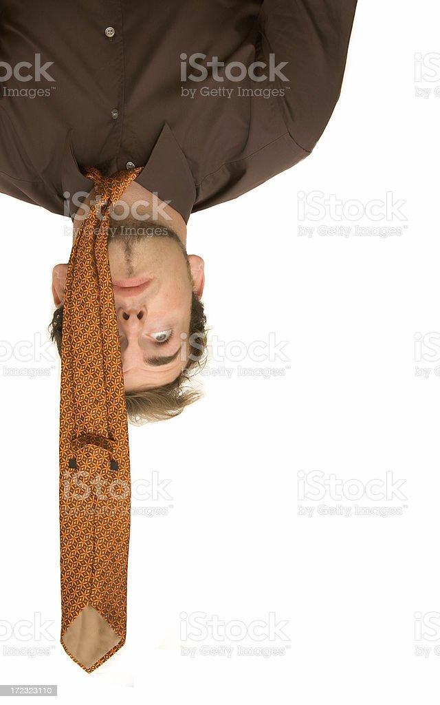 Businessman is hanging upside down having stress stock photo