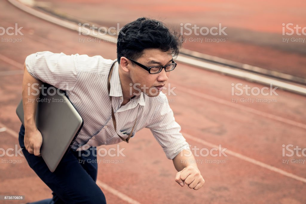 businessman is holding computer laptop while he is running on run lane. business man in action of beginning startup to run. start up business run to goal setting concept. stock photo