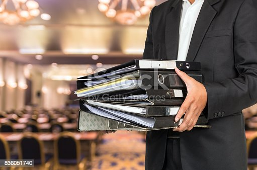 istock Businessman is holding many document folders on Abstract blurred photo of conference hall or seminar room background, business busy concept 836051740
