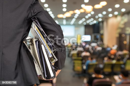 istock Businessman is holding many document folders on Abstract blurred photo of conference hall or seminar room with attendee background, back side, business busy concept 843060786