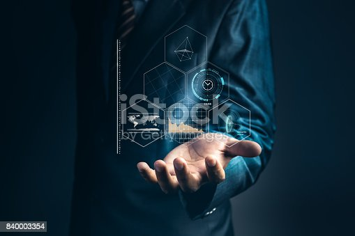 istock Businessman is holding to analyze marketing share information on hologram and connect to data with artificial intelligent system, Abstract of technology background and concept about internet of thing. 840003354