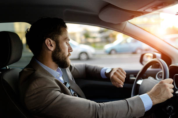 Businessman is Looking at Watch in His Car stock photo