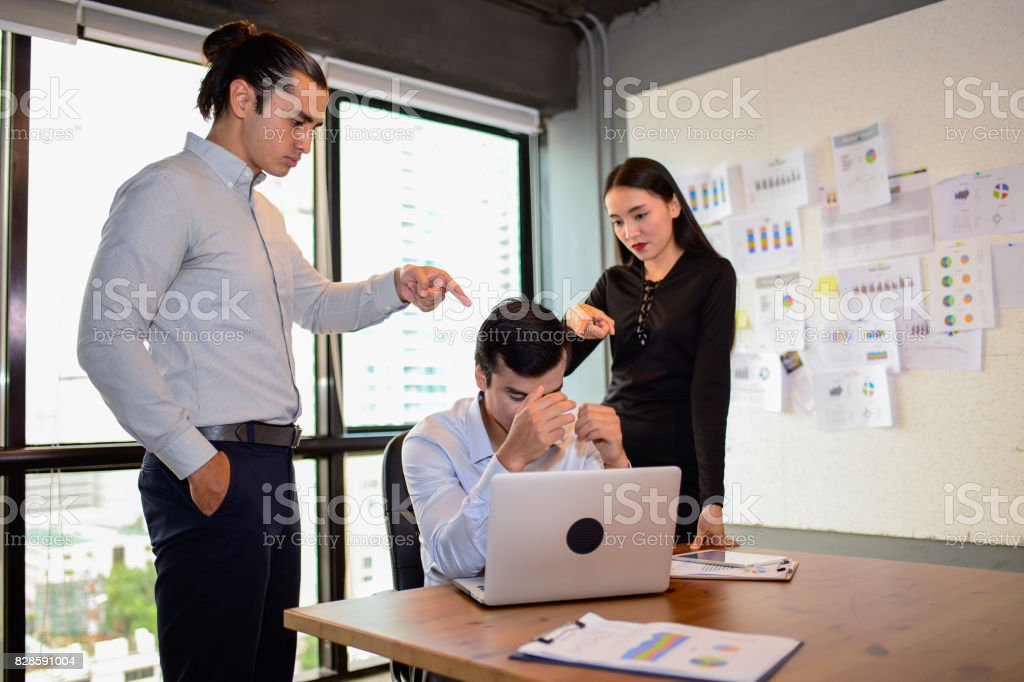 businessman is nervous and put his hand on head because his boss and colleague very agry and Pointing fingers at him. The concept of business mistakes. stock photo