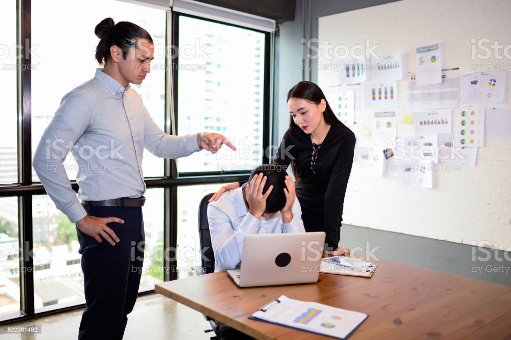 businessman is nervous and put his hand on head because his boss very agry and Pointing fingers at him, But his colleague are comforting him. The concept of business mistakes. stock photo