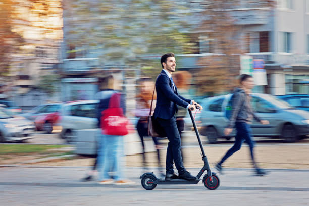 Businessman is riding electric scooter in the city stock photo