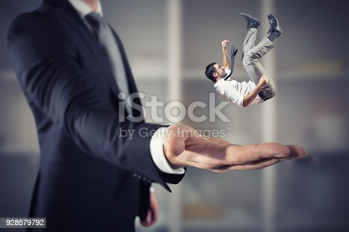 istock Businessman is saved from a big hand. Concept of business support and assistance 928579792