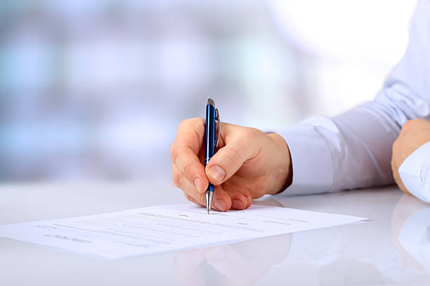 Businessman is signing a contract, business contract details Businessman is signing a contract, business contract details application form stock pictures, royalty-free photos & images