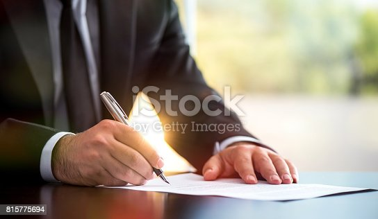 istock Businessman Is Signing A Legal Document In Office 815775694