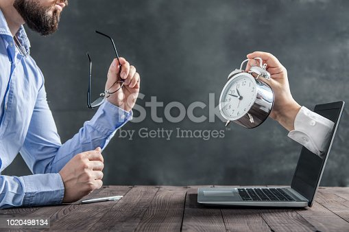 Businessman is sitting at the desk and is looking at the hand with clock coming out of the laptop. Metaphor of spending time at work