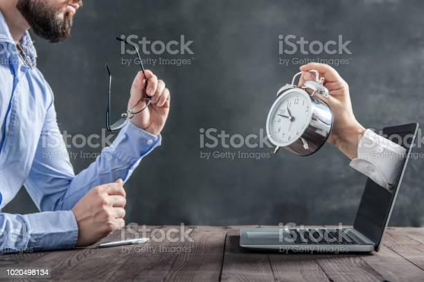 Businessman is sitting at the desk and is looking at the hand with picture id1020498134?b=1&k=6&m=1020498134&s=612x612&h=6tklzmxsa7qbrmiozk16jbtemfff7evvc6c9igixobo=