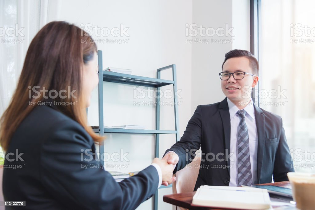 businessman is smiling while shaking hand with her partner after success in business negotiations . stock photo