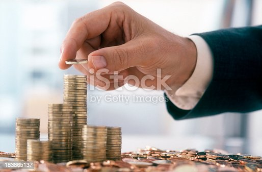 Hand of a mid adult man, wearing a siut, is stacking Euro coins. (2XL-File)