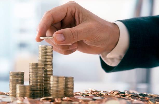 empresario está apilado de monedas - inversión fotografías e imágenes de stock