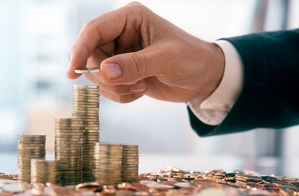 Businessman is stacking coins stock photo