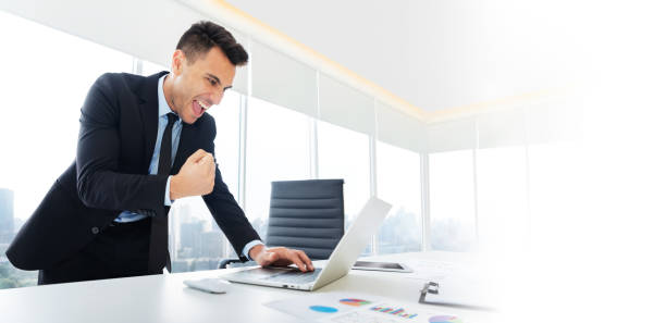 businessman is standing and looking at laptop. stock photo