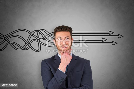istock Businessman is standing in front of blackboard with drawn arrows 673186630