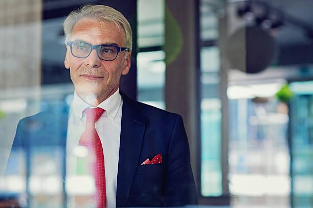 businessman is standing in his office - amministratore delegato foto e immagini stock