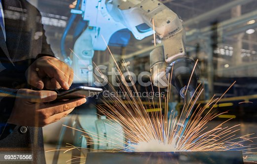 istock businessman is used smart phone control automate wireless Robot welding. It is industrial4.0 concept with double exposure 693576566