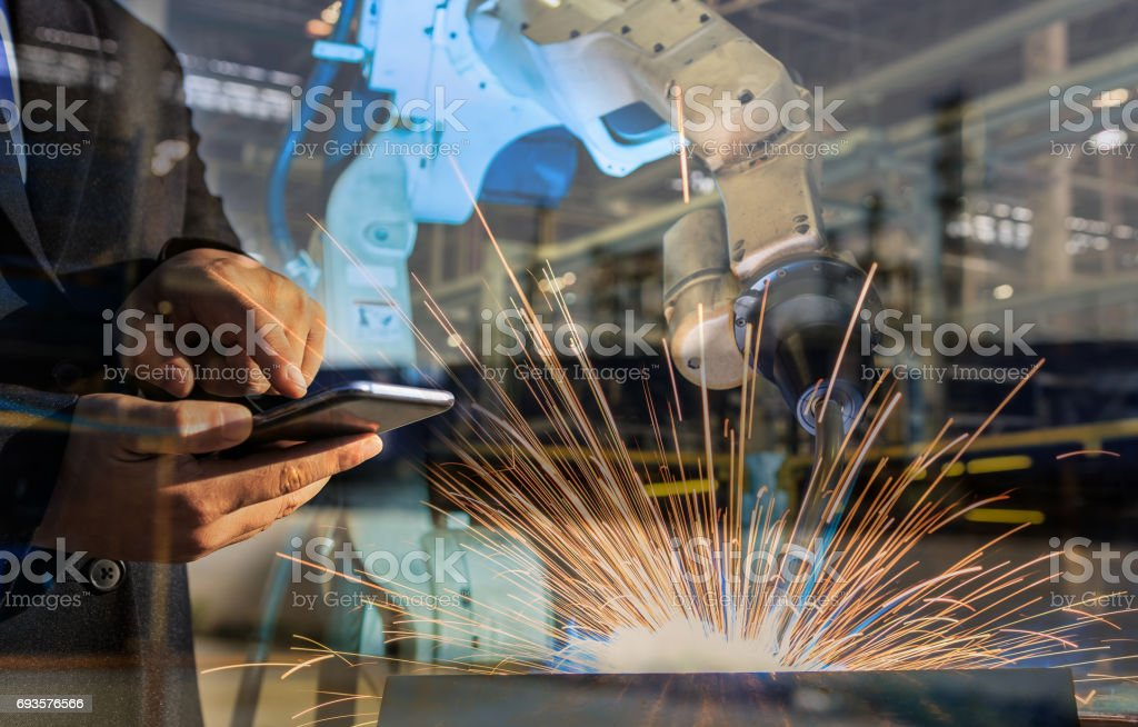 businessman is used smart phone control automate wireless Robot welding. It is industrial4.0 concept with double exposure stock photo