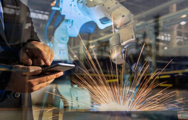 Geschäftsmann dient der Smartphone-Steuerung zu automatisieren, drahtlose Roboter Schweißen. Es ist industrial4.0 Konzept mit Doppelbelichtung – Foto